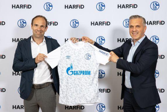 Alexander Jobst, Vorstand Marketing & Kommunikation des FC Schalke 04, und Harfid Hadrovic, Geschäftsführer der HARFID Unternehmensgruppe, präsentieren ein Shirt der neuen Trainingskollektion mit dem Logo des neuen Ärmelpartners HARFID.