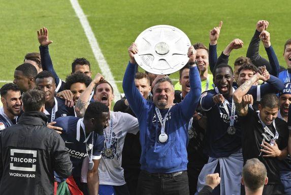 Die Spieler des VfL Bochum bejubeln, gemeinsam mit ihrem Trainer Thomas Reis (Mitte), den Gewinn der Zweitliga-Meisterschaft.
